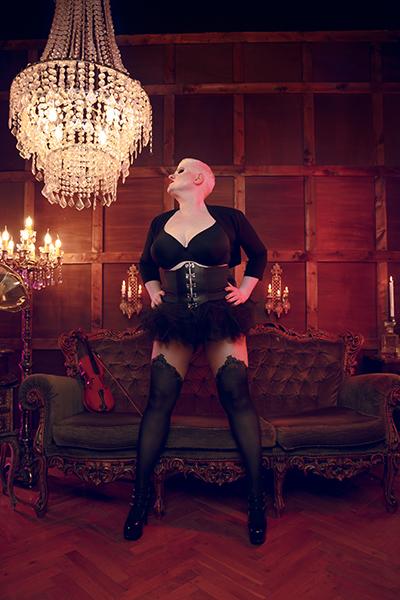 Lady Carmen trägt ein atemberaubendes Ensemble aus schwarzen Nylonstrümpfen mit bezaubernden Säumen, einem sehr knappen und einladendem Tutu. Ihre wundervolle Oberweite wird durch einen schwarzen eleganten BH bedeckt, dazu trägt sie eine schwarze Corsage mit Schnallen und einen schwarzen Bolero. Ihre strenge Kurzhaarfrisur steht ihr ausgezeichnet und sie hat ihre Hände forsch in die Hüften gestemmt. Sie befindet sich in einem opulentem Raum mit Kronleuchter, Geige, Kerzenbeleuchtung und einem plüschigen Sofa.
