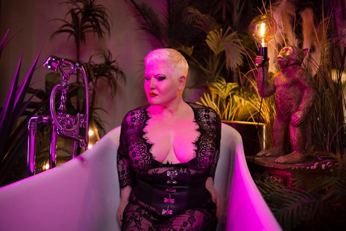 In rosa Licht getaucht sitzt Lady Carmen in einer Badewanne. Sie trägt ein wundervolles Spitzenoutfit zu ihrer Corsage. Der eng anliegende Catsuit rahmt sie sehr sexy ein. Neben der Badewanne steht die Stazue eines Affen, der eine Glühbirne hält. Du würdest alles dafür geben. für Lady Carmen die Glühbirne halten zu dürfen.