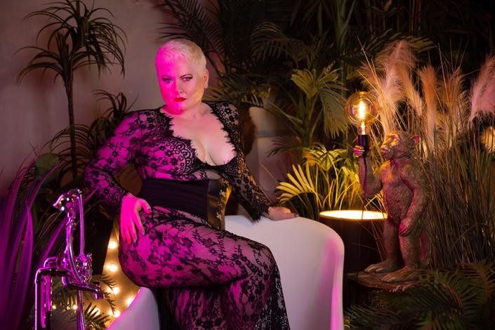 Lady Carmen sitzt in rosa Licht getaucht auf dem Rand der Badewanne und präsentiert dir einladend verführerisch ihren Po- ihr Blick ist erwartungsvoll, jedoch streng. Das zarte Spitzenoutfit umschmeichelt ihre Kurven und lässt viel haut durchblitzen. Du fühlst dich plötzlich sehr schwach.