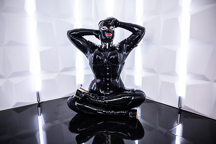 Wie eine schwarz glänzende Gottheit ist Lady Carmen in einem weiss strahlendem Raum auf dunklen Boden abgebildet. Sie trägt eine schwarze Vollgummierung, die verführerisch glänzt. Sie sitzt im Lotussitz und streicht sich mit ihren behandschuhten Fingern über die Vollmaske aus schwarzem Latex. Du fingerst nervös am Fläschchen mit dem Silikonöl, denn gleich wirst du Lady Carmen einölen und auf Hochglanz polieren.