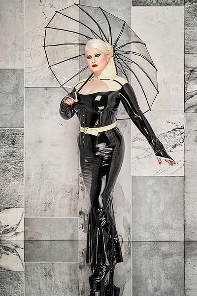 Lady Carmen steht vor einer grauen Marmorwand. Sie trägt ein sehr elegantes Latex Abendkleid. Das hat sie geschickt mit einem weissen Latexbolerojäckchen kombiniert. Das Korsett bringt ihre Figur perfekt zur Geltung - am liebsten möchtest du niederknien und sie verehren. Kokett hält sie einen durchsichtigen Regenschirm.