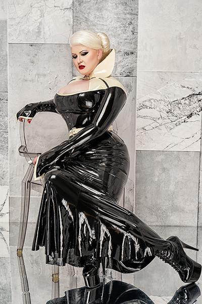 Lady Carmen sitzt vor einer schwarz weißen Marmorwand auf einem durchsichtigen Stuhl aus Plexiglas. Ihre Pose ist elegant, ein Arm auf der Lehne, der andere ruht entspannt auf ihrem Oberschenkel, ein Bein ist aufgestellt, das andere nach hinten weg gestreckt. Du bewunderst ihre schwarzen Lack Plateau Stiefel mit den spitzen Absatzen und träumst davon, ihr schwarzes glänzendes Latexkleid berühren und verehren zu dürfen. Ihr Blick lässt erahnen, dass sie gerade darüber nachdenkt, wie sich dich am besten benutzen kann.