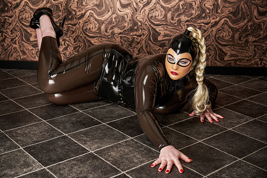 Lady Carmen trägt den rauchfarbenen Latexcatsuit wie eine zweite Haus. Sie räkelt sich auf dem Boden. Ihre tolle Kopfmaske aus Latex kommt toll zur Geltung,. vor allem der lange, blonde geflochtene Zopf.