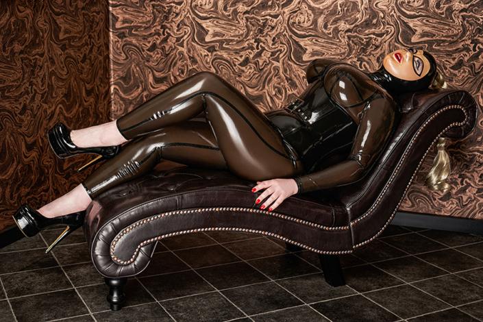 Ein in warmen Brauntönen gehaltener Raum. Eine braune Leder Chaiselonge. Darauf liegt Lady Carmen in anbetungswürdiger Pose auf dem Rücken und sieht an die Decke, ihre Beine locker überschlagen. Sie trägt geschlossene Plateau Lack Pumps in schwarz, einen rauchbraunen transparenten Latexganzkörperanzug und ein schwarzes Latexkorsett. Ihr Gesicht ziert eine Latexvollmaske. Du willst sie anbeten.